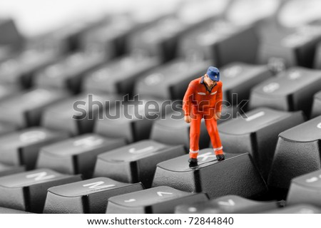 Figurine of worker looking into pit in computer keyboard