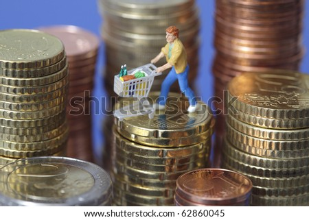 Figurine with shopping cart on top of euro coin stack