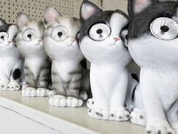 figurines of cats on a metal shelf. There are flashlights in the eyes. Great garden or home animal sculpture to light up at night. white kittens with gray and black parts.