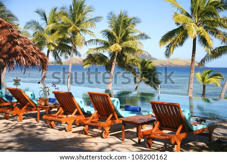 fiji with palm trees, sea, pool and deck chairs - stock photo