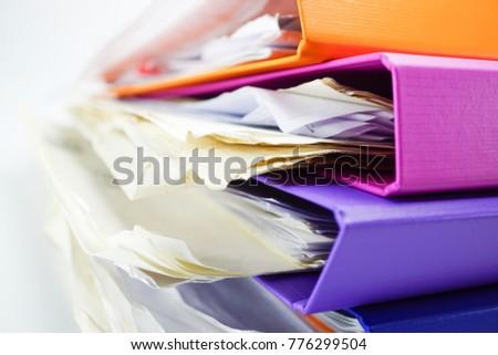 File Folder Binder stack of multi color on table in office. #776299504
