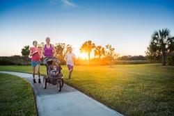 File name:Beautiful, fit young family walking and jogging together outdoors along a paved sidewalk in a park pushing a stroller at sunset