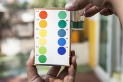 file of hand holding water ph testing test comparing color to indicated