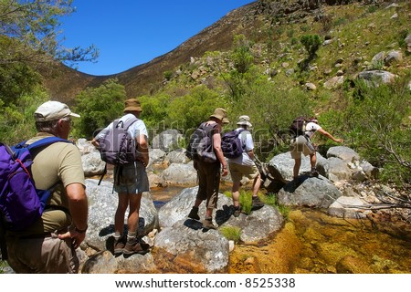 File of hikers walks across small river in awesome mountains. Shot in the Kromrivier - Du Toitskloof Nature Reserve, near Paarl, Western Cape, South Africa.