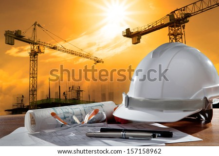 file of safety helmet and architect plant on wood table with sunset scene and building construction