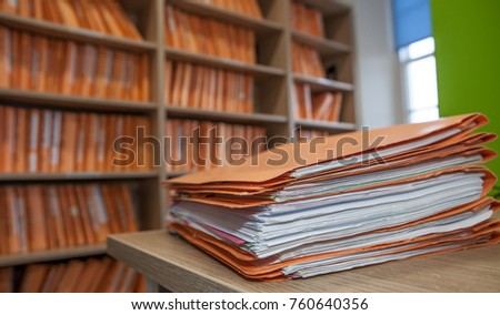 files on table infront of filing cabinet