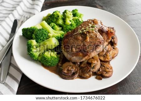 Filet Mignon in Mushroom Wine Sauce: Filet mignon steak with a creamy mushroom sauce served with broccoli florets