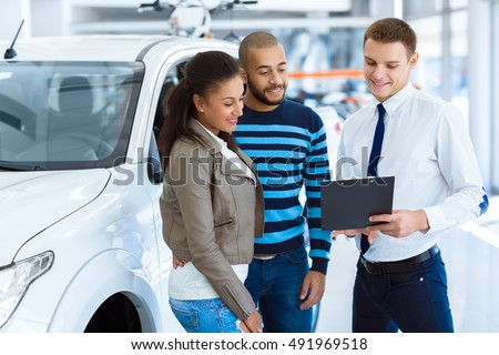 Filing document. Shot of a handsome salesman filing documents with his happy clients at the dealership Foto stock ©
