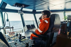 Filipino deck Officer on bridge of vessel or ship wearing coverall during navigaton watch at sea . He is speaking on GMDSS VHF radio, communication between vessels.