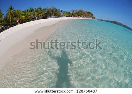Filipino seascape with beautiful weather, blue sky and clear water. Fish-eye lens. Shadow of person in water