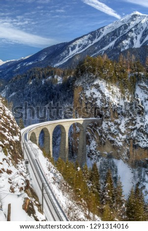 Filisur, Switzerland - January 19. 2019: The famous Landwasser Viaduct, which ia a wonder of Swiss mountain railway engineering in 1901 and a unesco heritage since 2008.