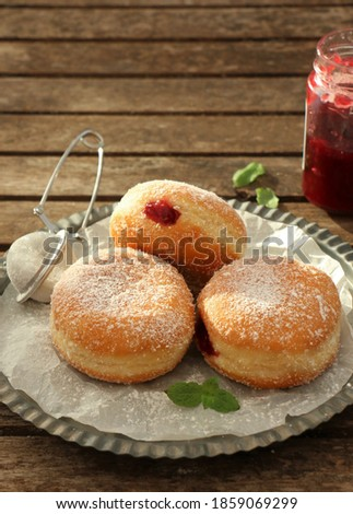 Filled Berliner style donuts / doughnut with Raspberry Jam Dusted with Icing Sugar. selective focus on rustic table ストックフォト ©