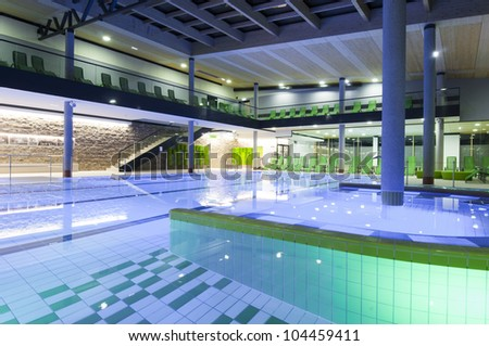 filled indoor swimming pool with colored tiles and illumination