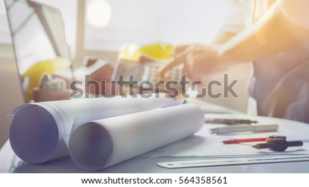 filled with building plans and background of Town planning,business man working with laptop and blueprints,landscape architects sitting  behind  the architectural business plan and calculator