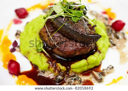 Fillet of beef with elk liver served with mashed potatoes and peas, creamy mushroom stew and red wine and blueberry sauce