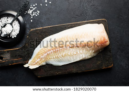 Fillet of fresh sea white cod fish on a dark background with sea salt and young green peas. Healthy food ingredients for the whole family. Top view. Flat lay ストックフォト ©
