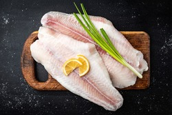 Fillet of raw pangasius fish with lemon and green onion on cutting board on dark background. Top view.