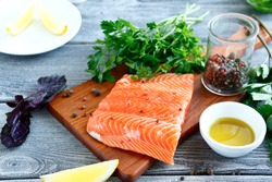 Fillet  Salmon with fresh herbs and lemon on a board. Seafood