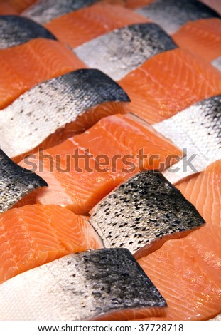 Fillets of salmon arranged in a patchwork display at a fish market