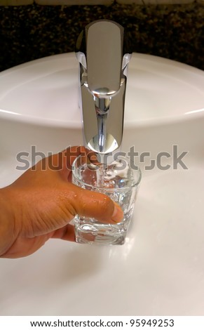 filling a glass of fresh water from water tap
