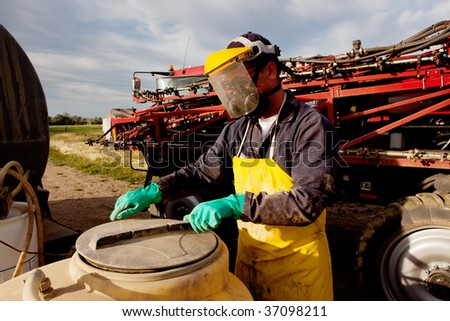 Filling a high clearance sprayer with chemical and water with proper safety equipment