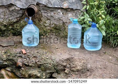 Filling by water of bottles from a source