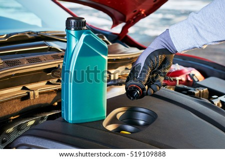 Filling engine oil in modern car. Winter service for safe driving.