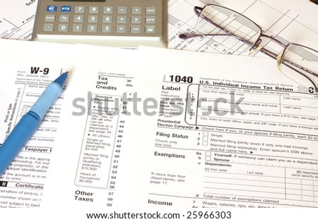 filling federal tax forms with a blue pen