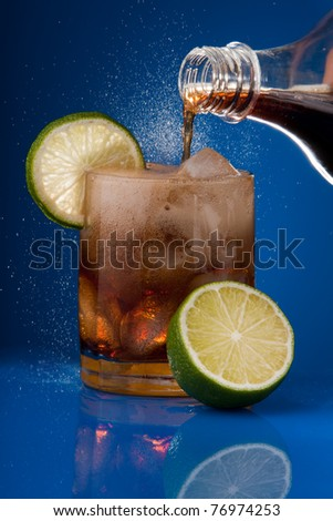 Filling glass with cola sprinkling from bottle with ice and lime