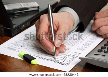 Filling in a 1040 individual tax form with calculator and laptop