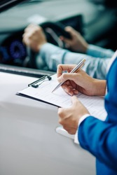 Filling questionnaire for customer before test drive in car dealership