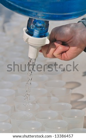 Filling the Cups - person filling plastic cups with water