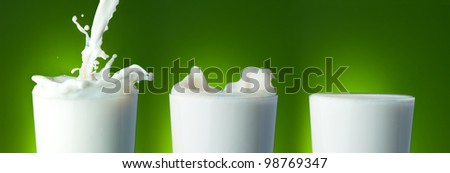 Filling the glass with milk with splashes on green - stock photo