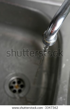 Filling the metallic kitchen sink with water