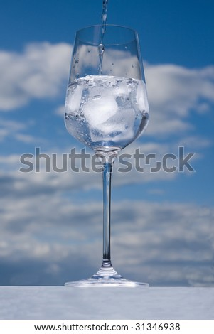filling water in glass with ice on cloudy sky background