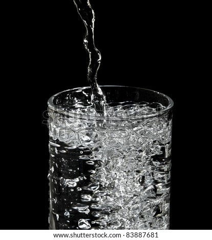 filling water into glass and black background