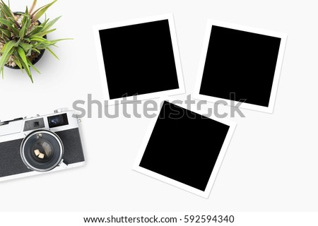 Film camera with blank picture frames are on top of white table.