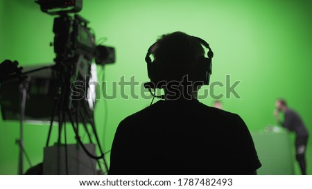 Photo of  Film crew in green studio shooting video. Chroma - technology of combining two or more images or frames in single composition. Cameraman,director,crew. Filmmaking industry.