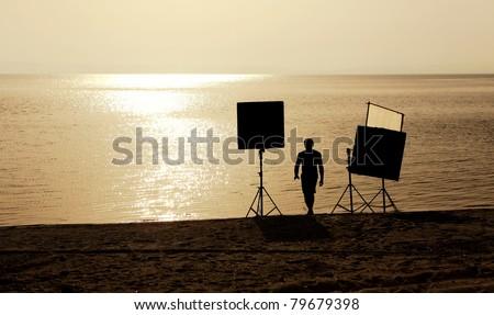 film crew setting up scene on a beach