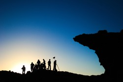 film crew silhouette at sunset in mountains