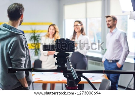 Film director discussing movie plan with the actors in the office scene. Lights pointing to the actors