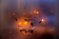 Film grain effect. Close-up view of hand print on glass misted window. Blurred orange night street light in the background. Selective focus. Night robbery theme.