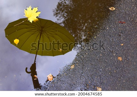 Film grain effect, lomography stylization. Yellow umbrella is reflected in a puddle on the asphalt. Autumn rainy weather.  Photo stock ©