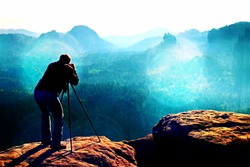 Film grain effect.  Professional on cliff. Nature photographer takes photos with mirror camera on peak of rock. Dreamy fogy landscape, spring orange pink misty sunrise in a beautiful valley below.