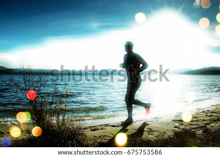 Film grain effect. Silhouette of tall sport active man running and exercising on beach at busch below sunset.