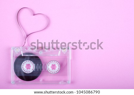 Film in a shape of heart from Compact Cassette. Love for music and songs. Pink background. #1045086790