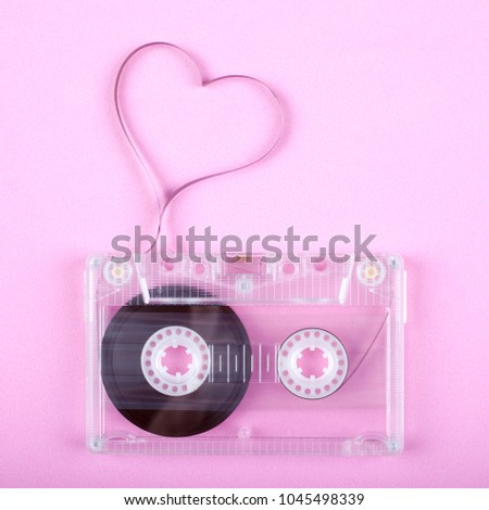 Film in a shape of heart from Compact Cassette. Love for music and songs. Pink background. #1045498339
