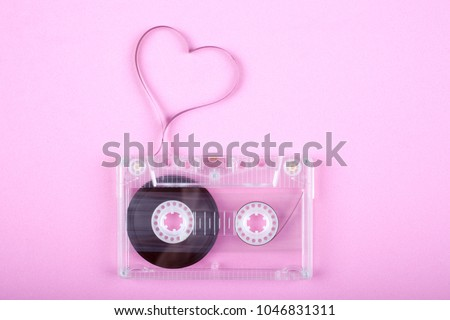 Film in a shape of heart from Compact Cassette. Love for music and songs. Pink background.