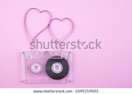 Film in a shape of heart from Compact Cassette. Love for music and songs. Pink background. #1049259005