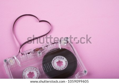 Film in a shape of heart from Compact Cassette. Love for music and songs. Pink background. #1059099605
